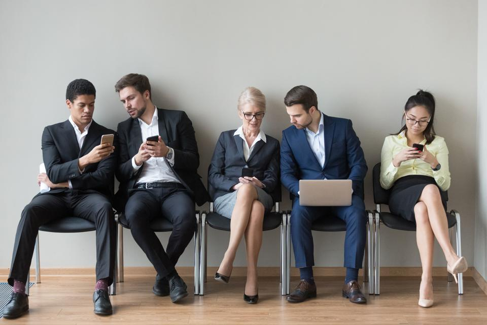 Work candidates sit in queue using gadgets before interview