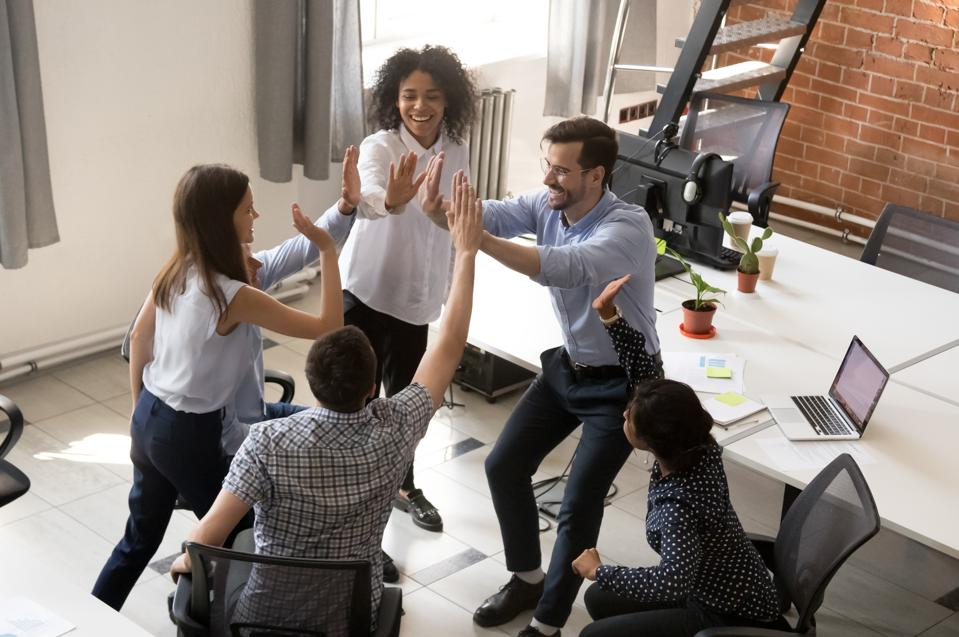 Excited happy multiracial office team giving high five celebrating success