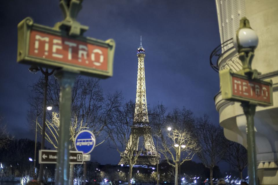 Eiffel Tower illuminated seen in the night with a Metro...