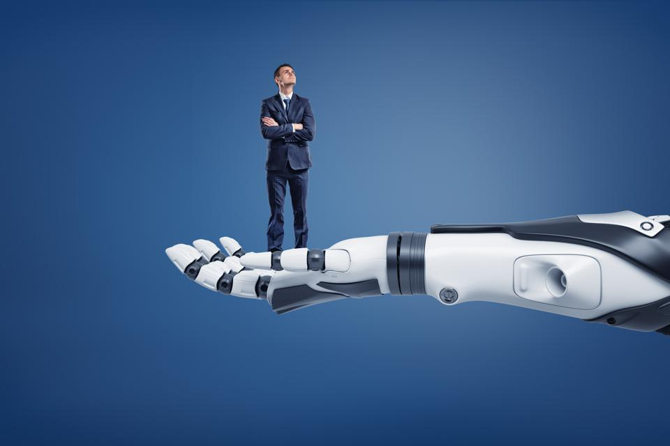 A small thinking businessman looks up while standing on a huge robotic arm.