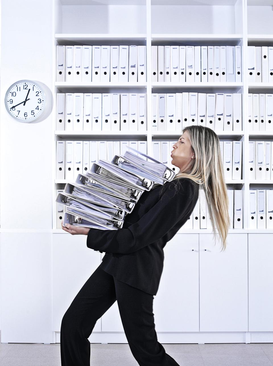 Businesswoman carrying a stack of work files -- how to cope when you are asked to take a new role