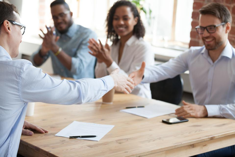Excited employees handshake at meeting after successful negotiations