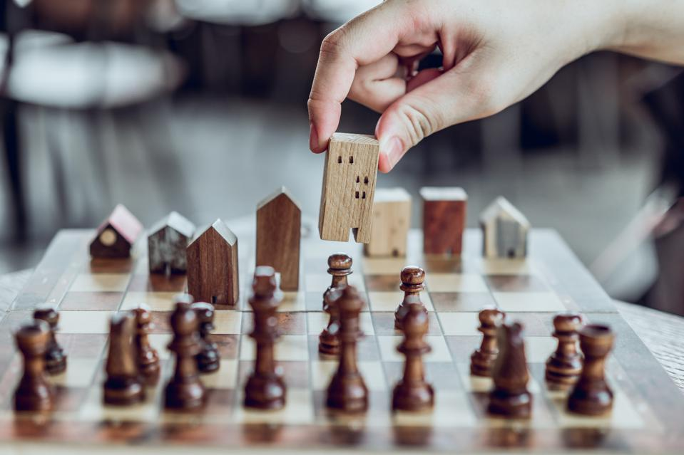 Hand choosing mini wood house model from chess game, Choose what's the best. A symbol for construction ,ecology, loan, business financial district and commercial ,success and leadership concepts.