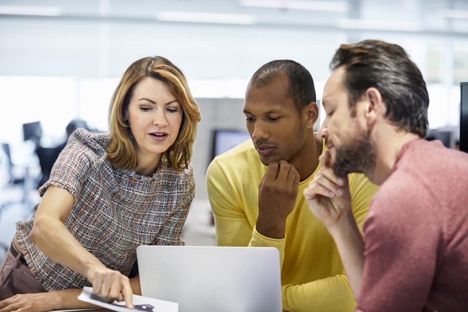 Businesswoman discussing over plan with coworkers