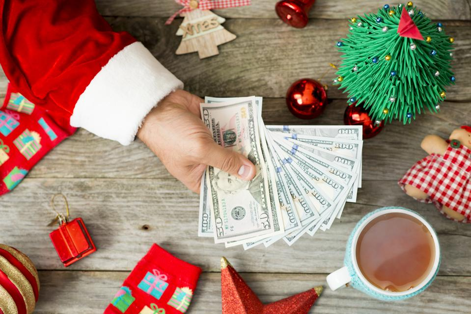 Santa Claus hand holding cash money against Christmas background, suggesting high expenses during the holidays