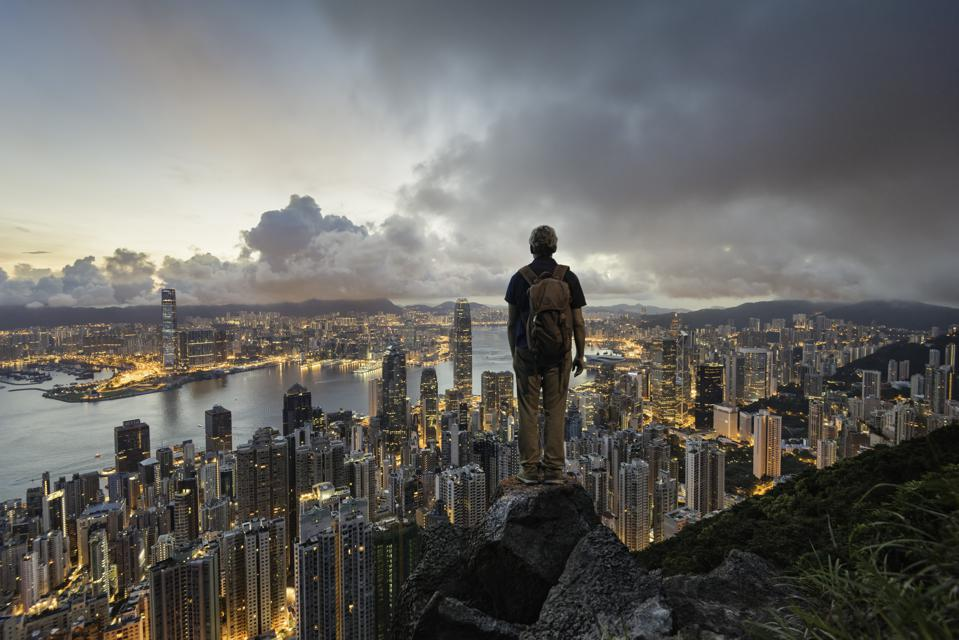 A man standing on a rock overlooking hong kong skyline at dawn, from Victoria Peak