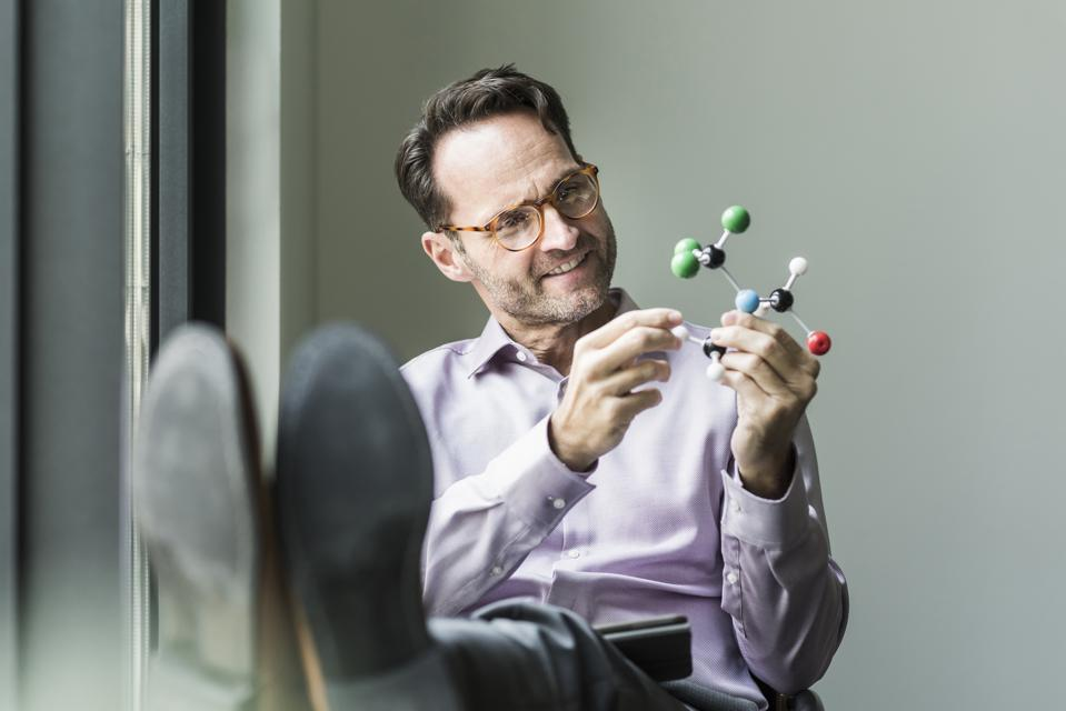 Portrait of smiling man with atomic model