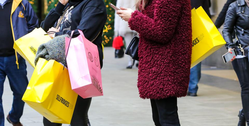 Women are seen with Selfridges shopping bags on London's...