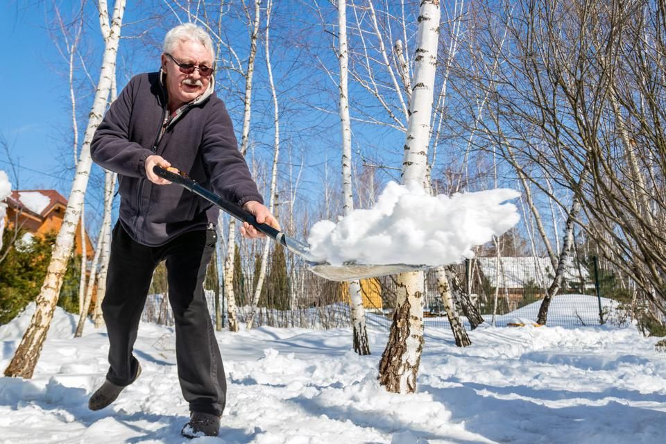 Elderly person removing snow in garden after heavy snowfall.