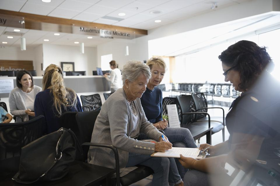 Female nurse discussing insurance paperwork with senior patient in clinic waiting room