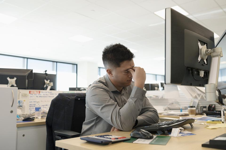 Tired businessman at computer in office