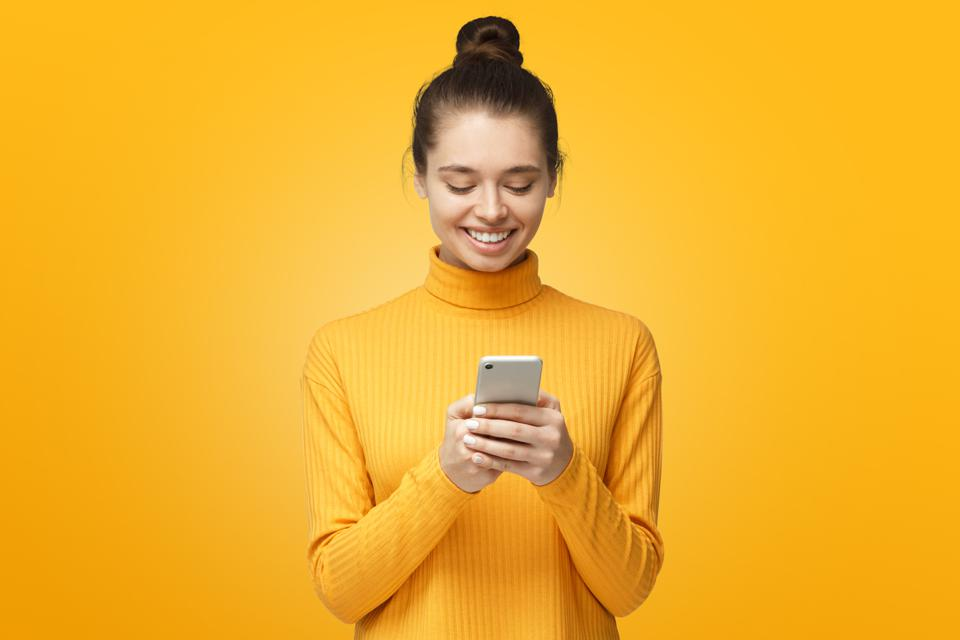 Yong pretty female standing isolated on yellow background looking at screen of phone, smiling nicely while chatting