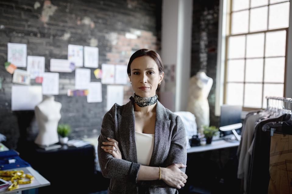 Portrait confident, determined female fashion designer in office