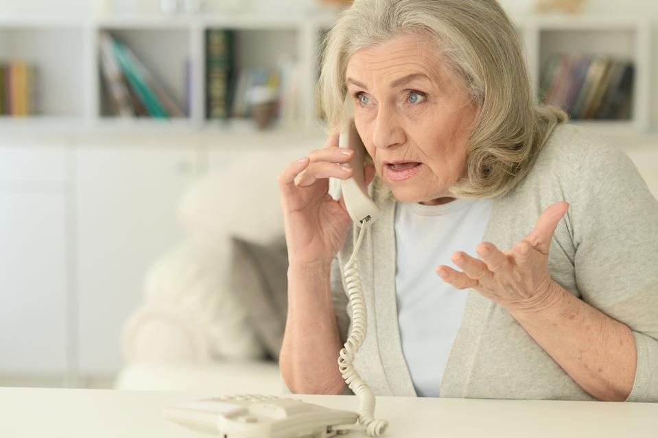 upset senior woman with  phone