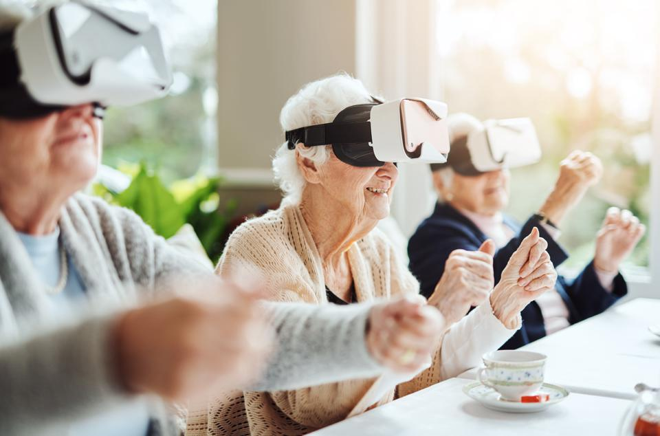 Older women using virtual reality goggles in a retirement home.