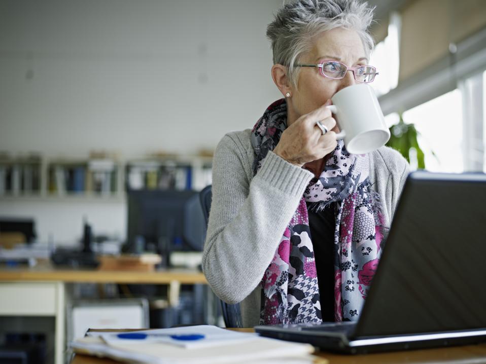 Businesswoman sitting in office drinking coffee