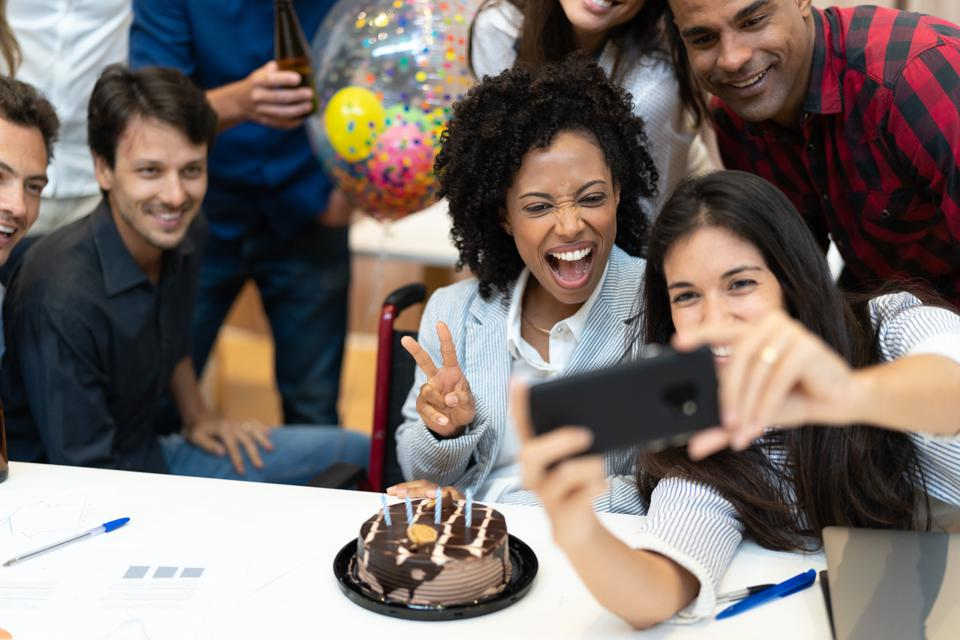 Business colleagues taking a selfie at birthday party at work