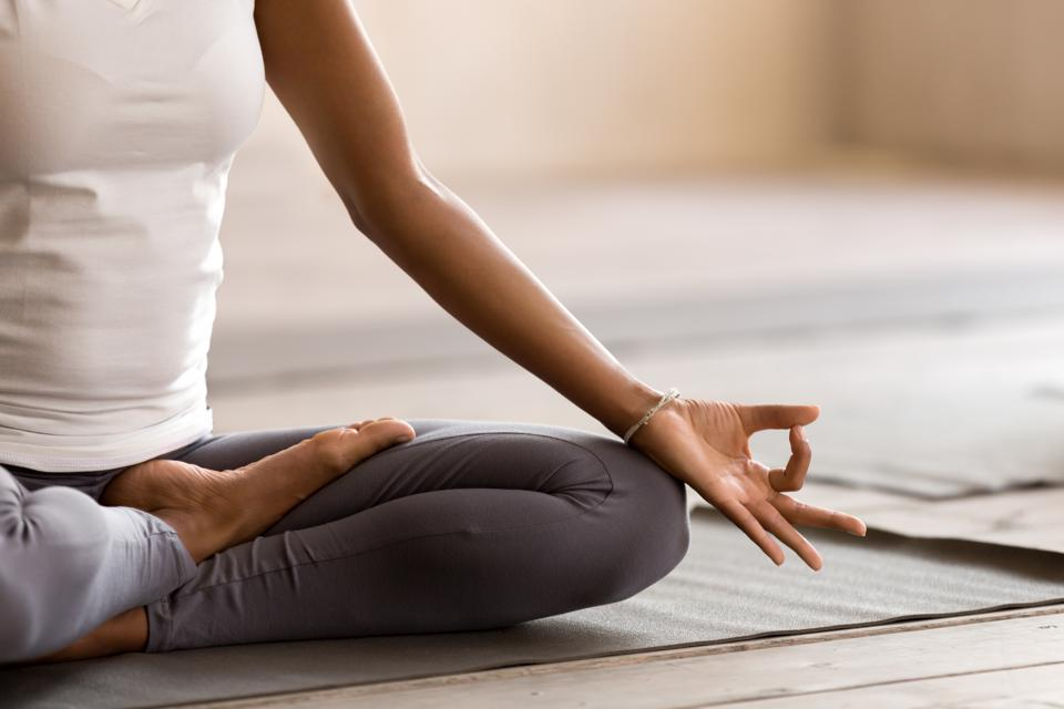 Yogi's black woman practiced yoga, breathing, meditating, doing Ardha Padmasana exercises, Half Lotus poses with mudra movements, exercising, indoor close ups. Well-being, the concept of health