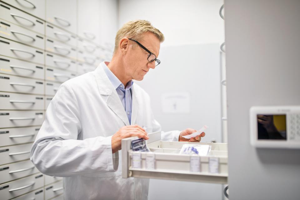 Chemist looking for the medicines in storage cabinet
