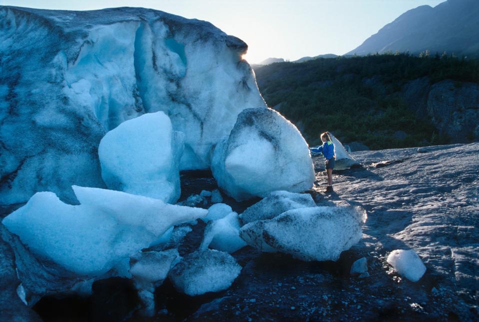 Woman hiker explores touches melting Exit Glacier Kenai Fjords National Park Alaska