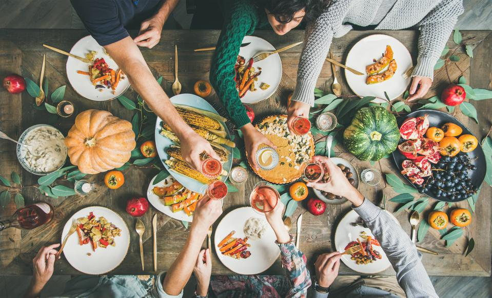 Friends clinking glasses at Thanksgiving Day with vegetarian meals