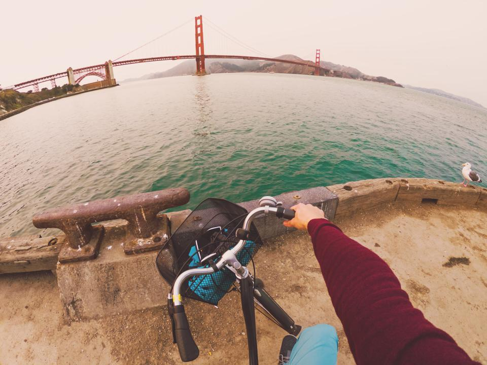 Guy contemplating the Golden Gate Bridge with bicycle.