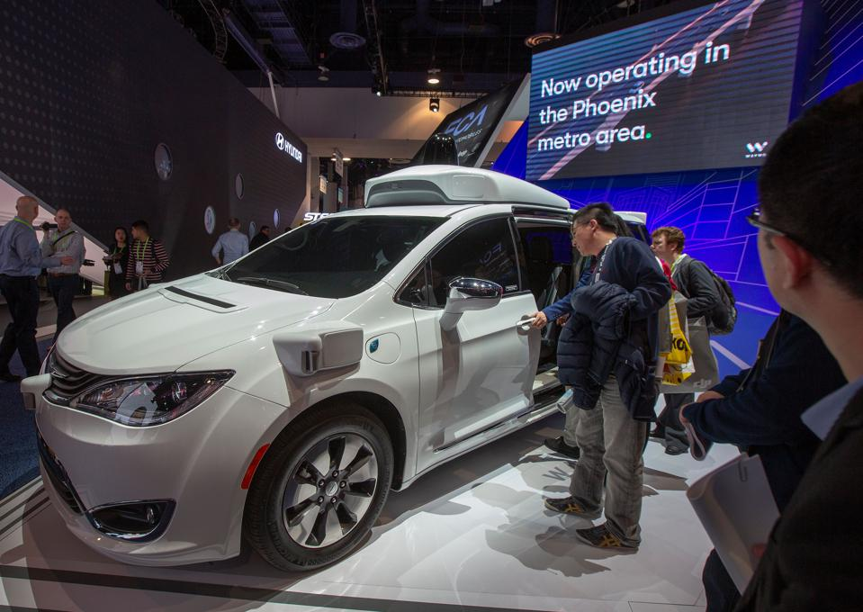 People look at a self-driving Waymo minivan at the Las Vegas Convention Center during CES 2019 on January 9, 2019.