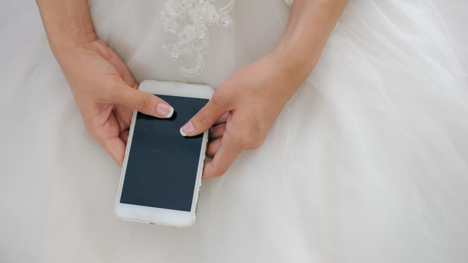A partial view of a bride in a white gown holding mobile phone