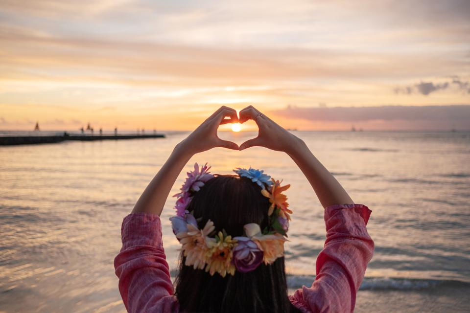 Woman with flower head crown making heart shape with hands