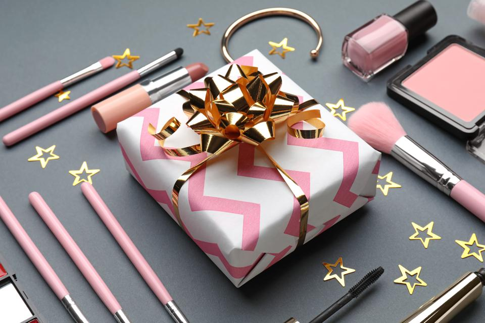 Composition with gift box and set of decorative cosmetics on grey background
