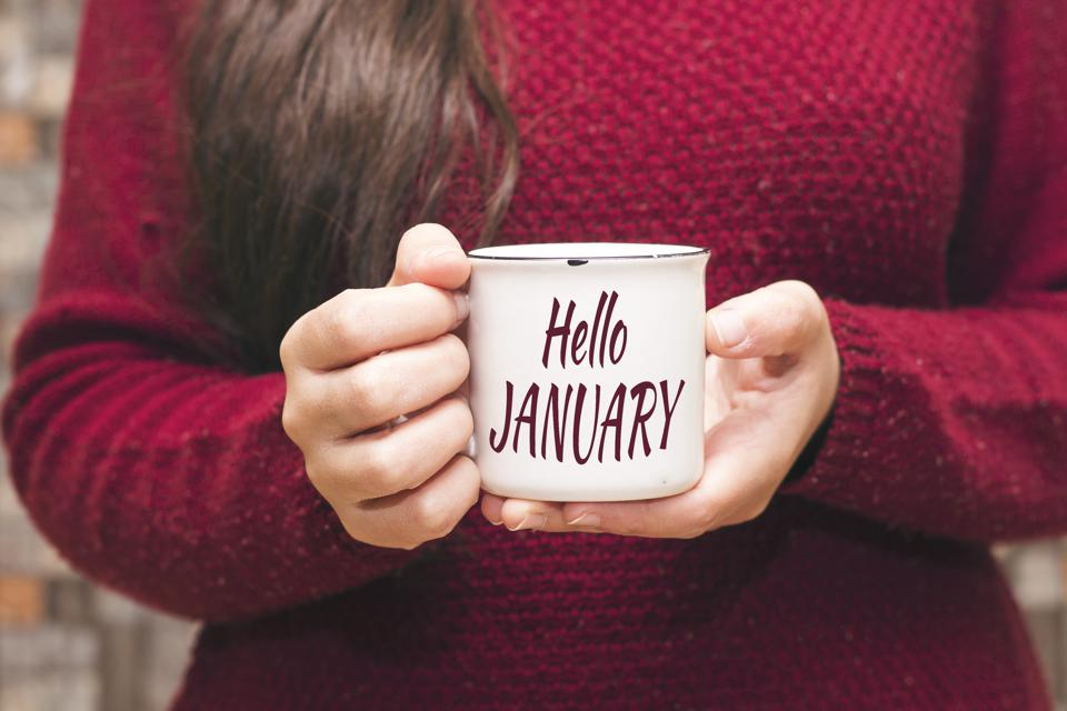 hello january text on cup and woman drinking a coffee