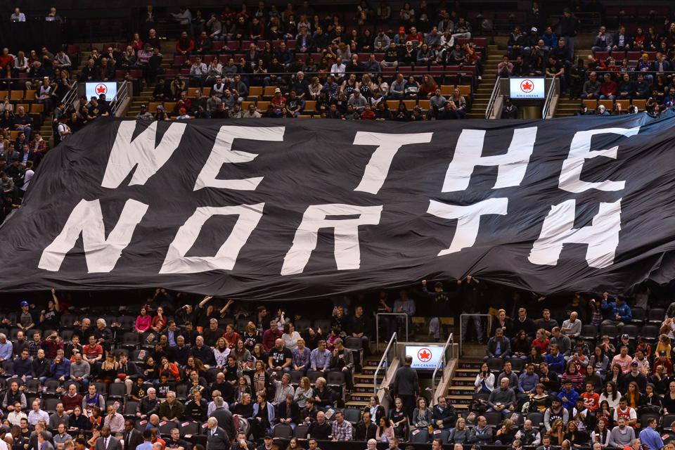 Toronto Raptors fans passing a ″We The North″ banner through Scotiabank Arena during halftime of a game.