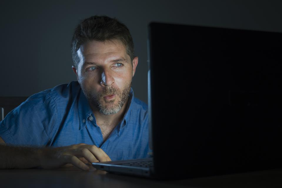 young aroused and excited sex addict man watching porn mobile online in laptop computer light night at home desk in pornography addiction and internet pornographic content concept