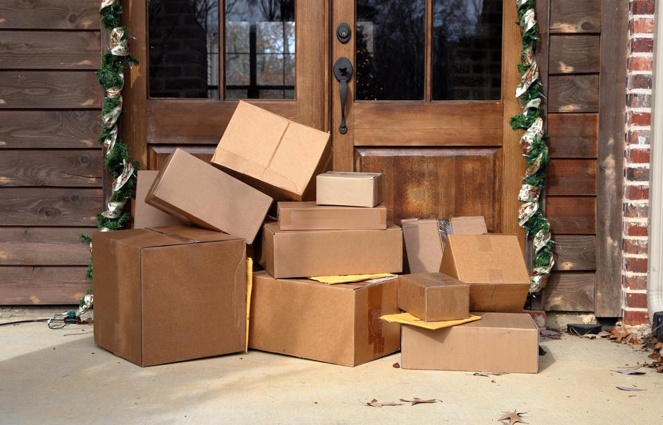 Shipping boxes near door on front porch of house during holiday shopping season