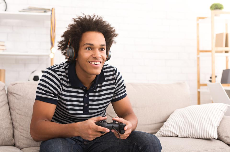 Teenager playing video games at home