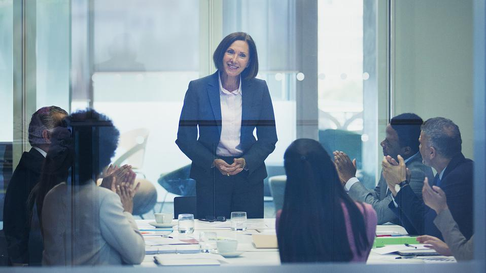 Colleagues clapping for businesswoman leading conference room meeting