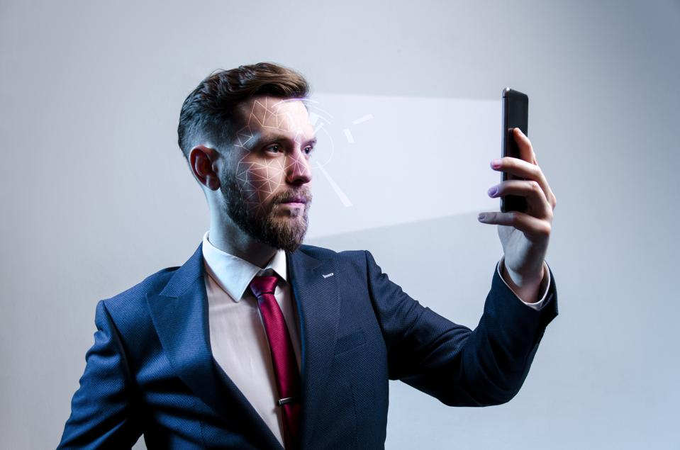 Young modern man in suit using facial recognition softer