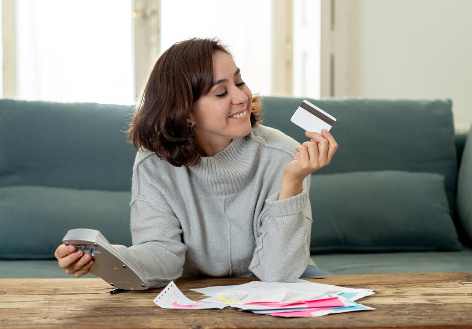 Young attractive latin business woman looking happy and satisfied with credit debit card advantages and use and accounting costs, charges, taxes and mortgage with calculator on sofa at home. .