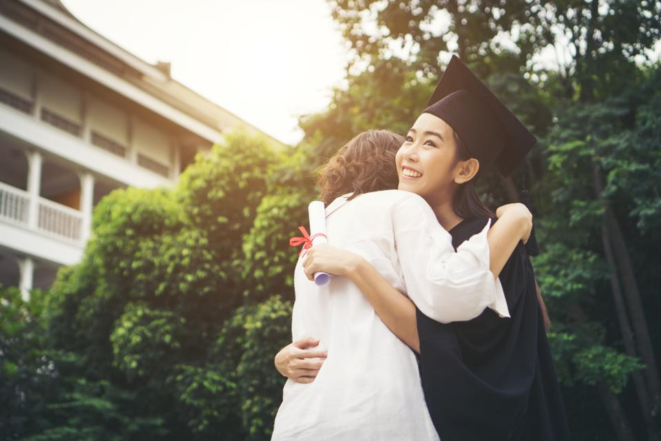 Cheerful Woman In Graduation Gown Embracing Mother While Standing Outdoors