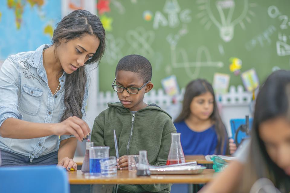 Teacher helping a young boy with chemistry