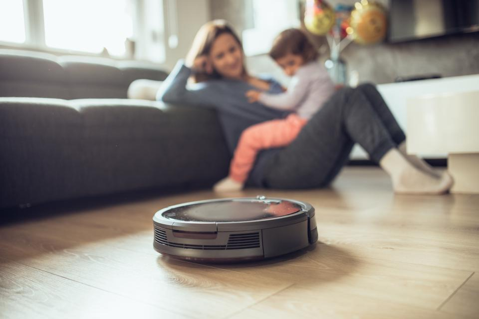 Robotic Vacuum Cleaner Cleaning Floor While Mother and Daughter Relaxing Together