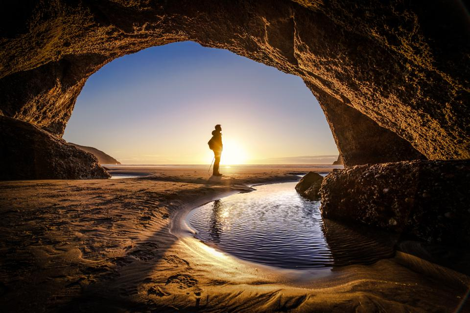 Concept image of a man standing in front of a cave exit