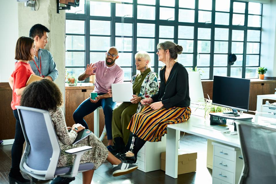 Business colleagues in meeting with female amputee sitting on desk
