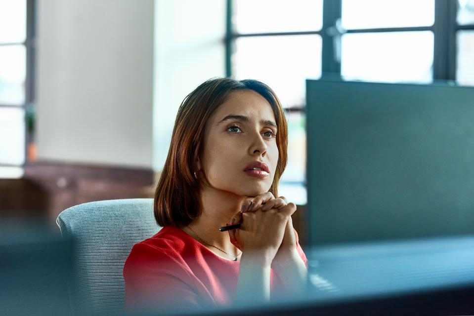 Candid portrait of Hispanic businesswoman deep in thought at desk