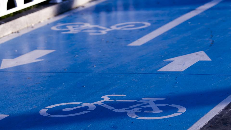 Two lane bicycle road detail with blue background and white images of bicycles and arrows.