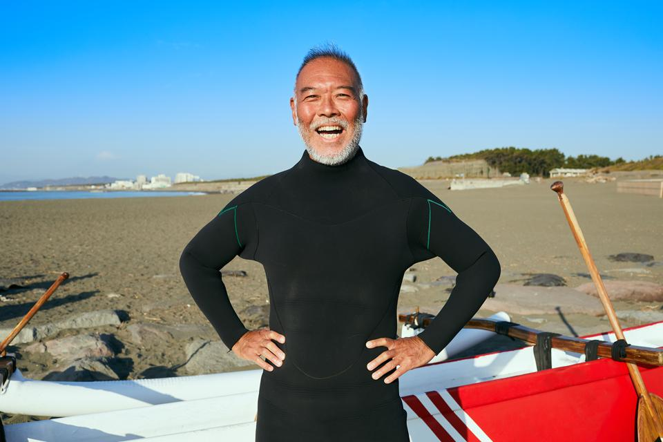 Portrait of smiling legendly surfer lean to canoe in beach at morning.