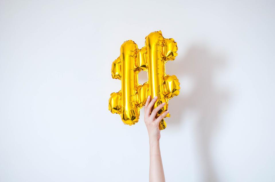 A golden-colored balloon symbol hashtag