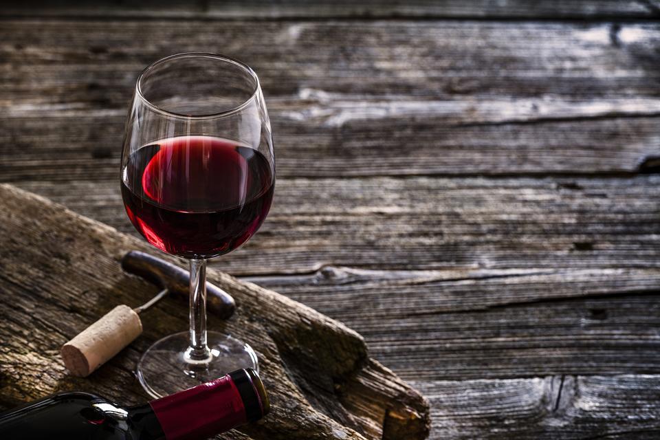 Wineglass, wine bottle, vintage corkscrew and cork stopper