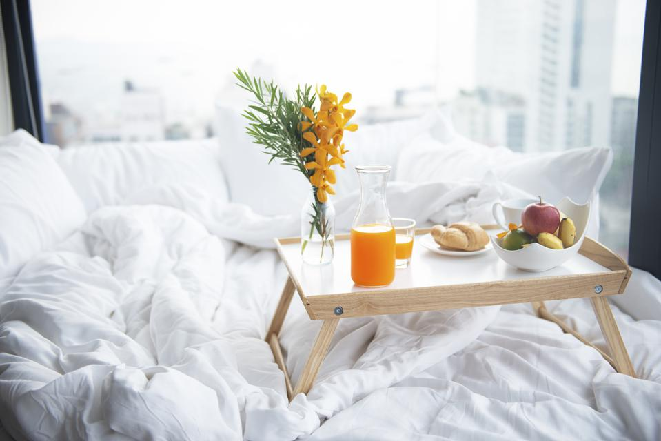 Soft breakfast food, orange juice, bread and milk on the small tabel on the white bed.