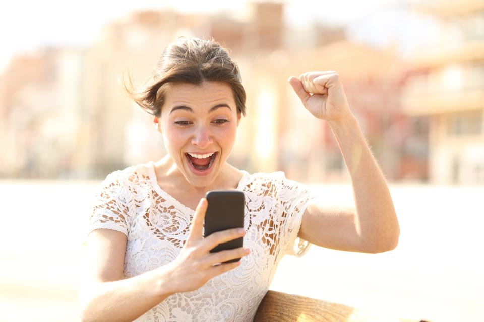 Excited woman reading amazing news on a phone